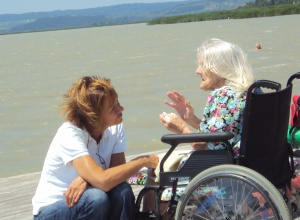 Alte Frau im Rollstuhl im Gespräch mit junger Frau, beide am Seeufer