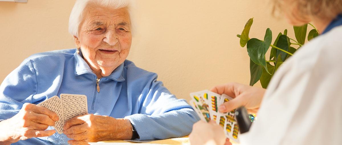 Alte Frau beim Kartenspielen